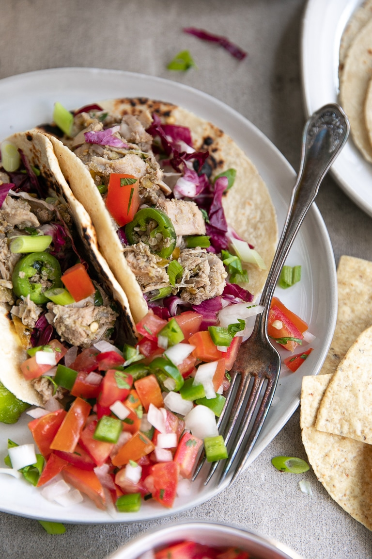 chile verde pork tacos served with pico de gallo and cabbage in flour tortilla