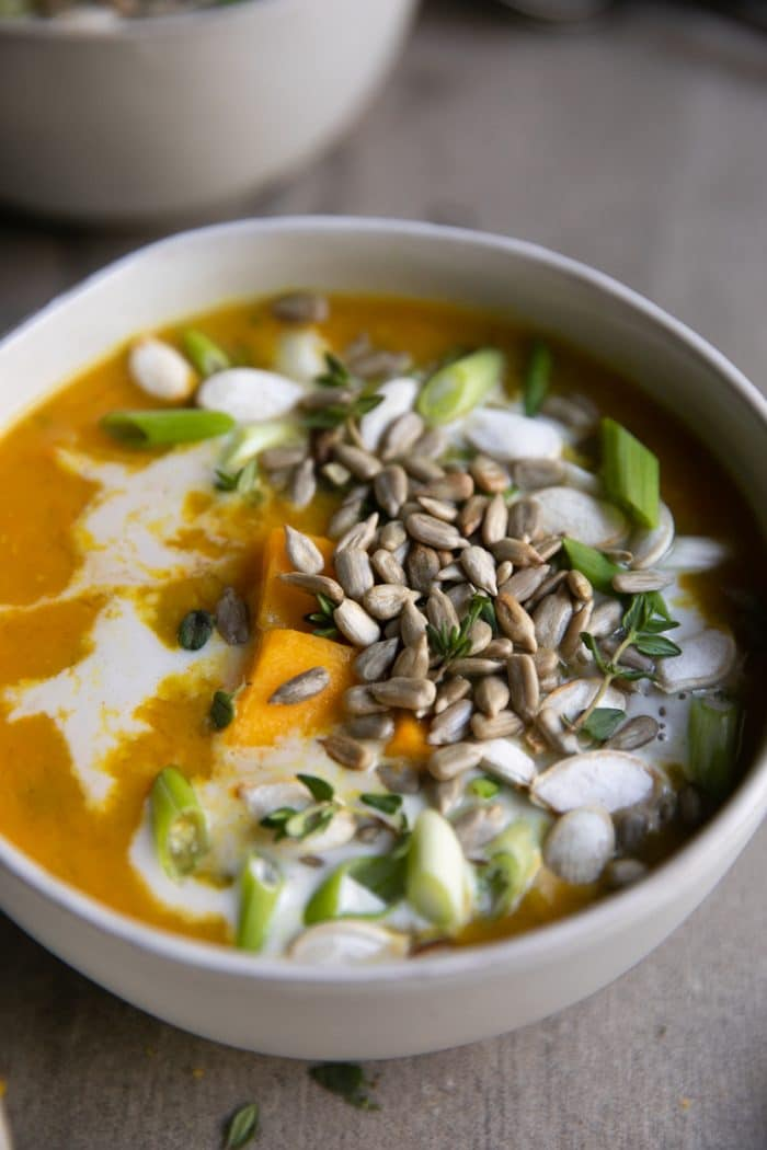 white bowl full of Healthy Curry Lentil Soup covered with seeds
