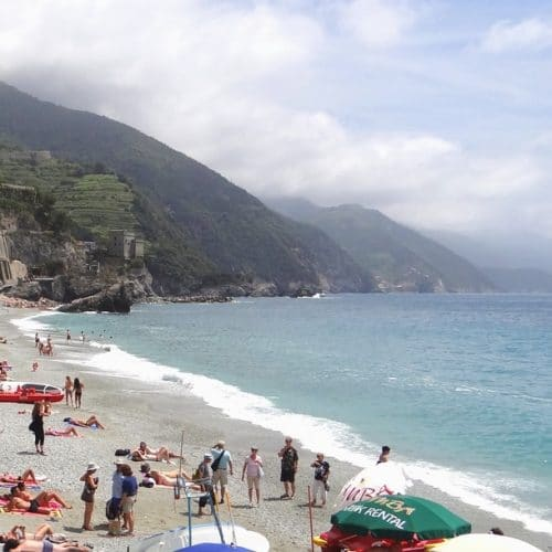 A group of people on a beach near a body of water with Monterosso al Mare in the background