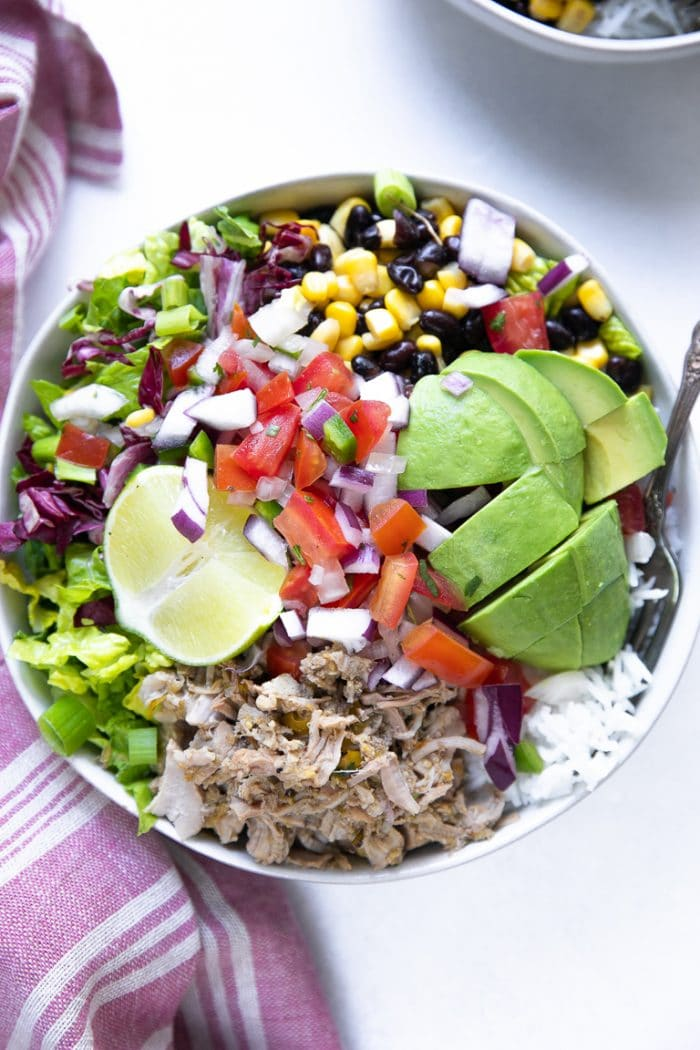 Bowl filled with white rice, chili verde pork, avocado, pico de gallo, lettuce, corn and beans.
