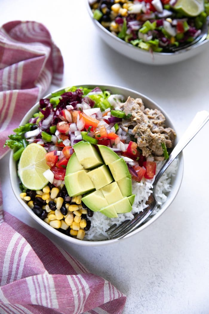 Prepared chili verde pork burrito bowls with pico de gallo and avocado
