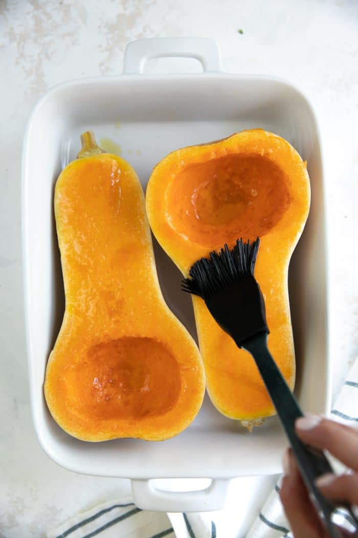 Brushing a halved butternut squash with olive oil