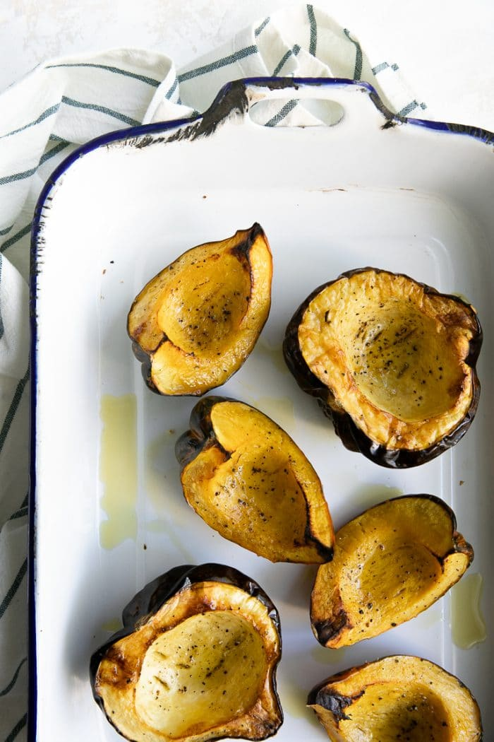 Roasted halves and quarters of acorn squash in a large roasting pan.