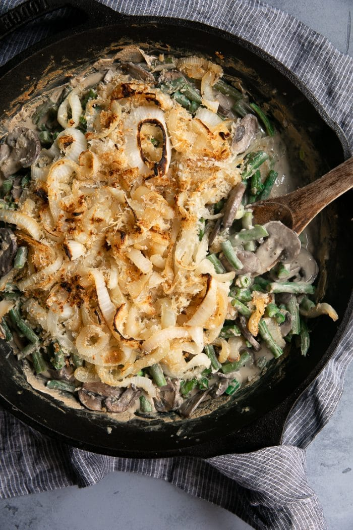 Cast Iron Skillet filled with homemade Healthy Green Bean Casserole Recipe made with homemade cream of mushroom soup and fried onions.