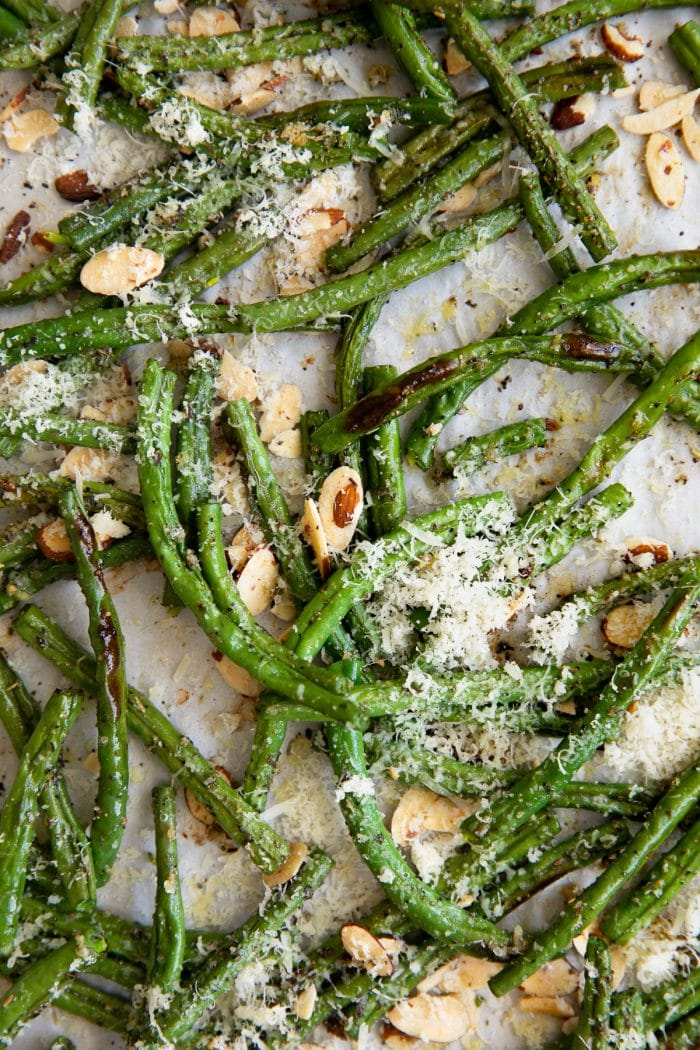 Oven roasted green beans on a large baking sheet sprinkled with fresh parmesan cheese and candied slivered almonds.