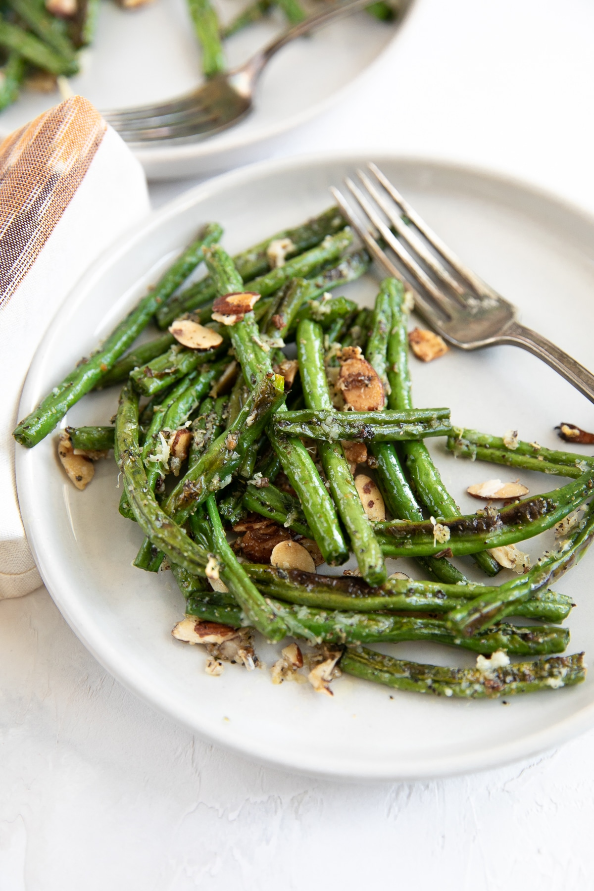 Small serving plate with oven roasted green beans tossed in shredded parmesan cheese and candied slivered almonds.