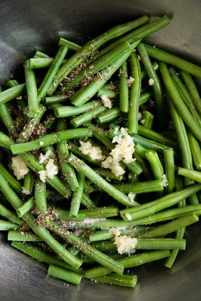 Fresh green beans in a large mixing bowl with garlic, salt, and olive oil.