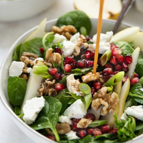 Balsamic vinegar salad dressing being poured into a white bowl filled with spinach, pear and feta salad.