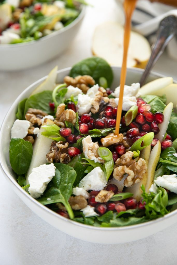 Salad bowl filled with spinach and feta cheese drizzled with balsamic vinaigrette.