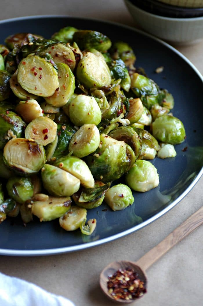 Sautéed Brussels Sprouts with Lemon and Garlic on a black serving plate