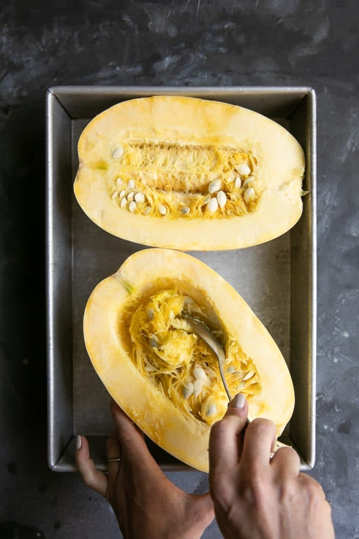 removing seeds from a halved and uncooked spaghetti squash
