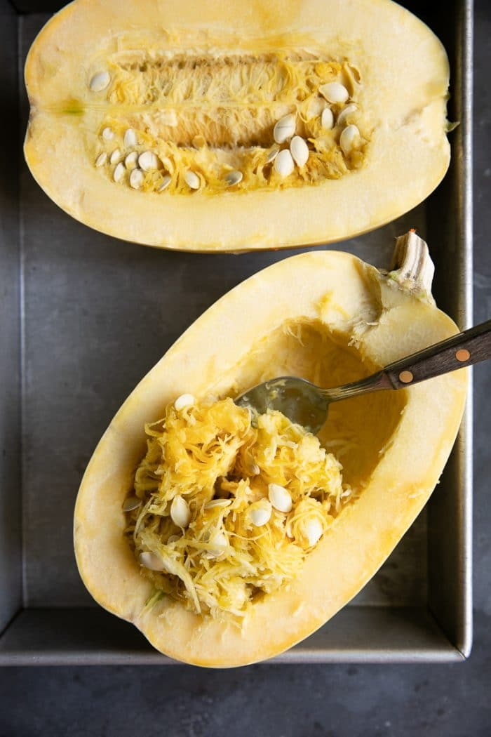 Close up image of seeds being scooped out of a halved spaghetti squash