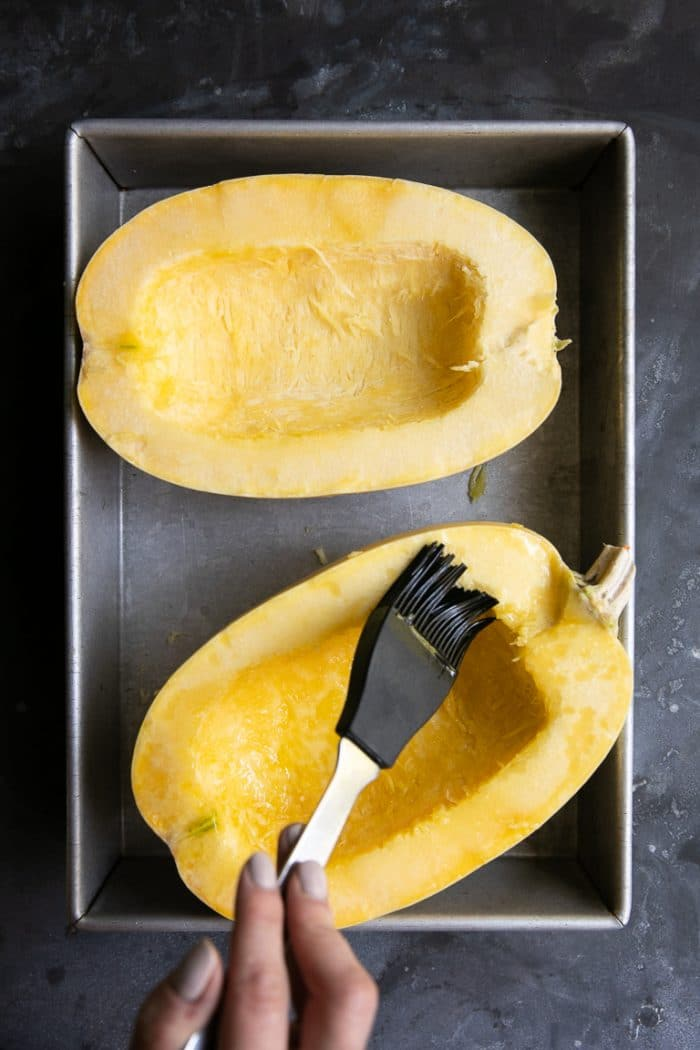 Brushing inside of the spaghetti squash with olive oil.