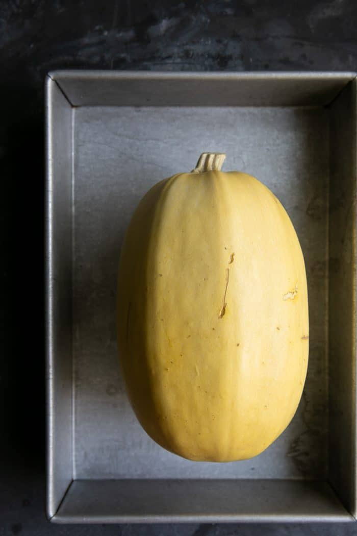 whole spaghetti squash in a baking pan