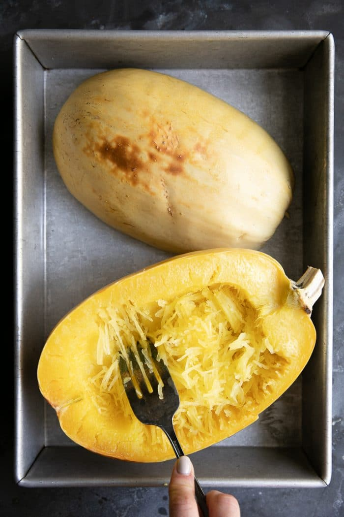 Fully cooked spaghetti squash in a metal baking pan.
