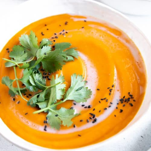 Two white soup bowls filled with ginger carrot soup and garnished with coconut cream, cilantro, and black sesame seeds.