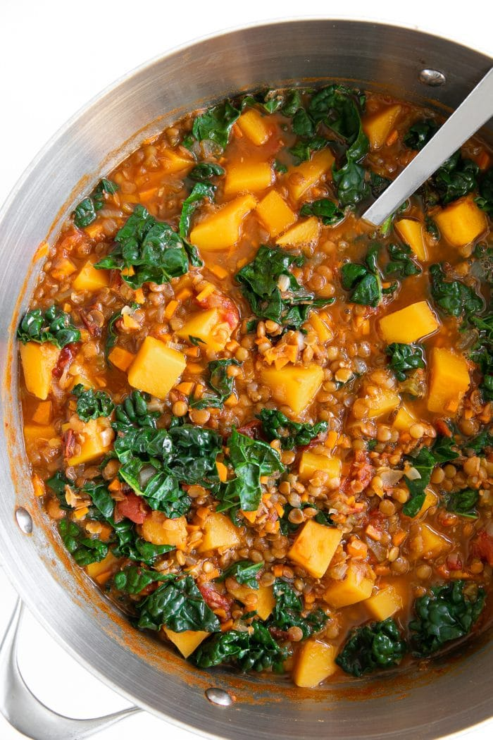 Simmering butternut squash and lentil stew with kale and chipotle.