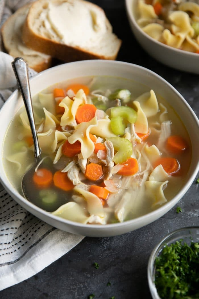White bowl filled with chicken noodle soup and served with buttered bread.