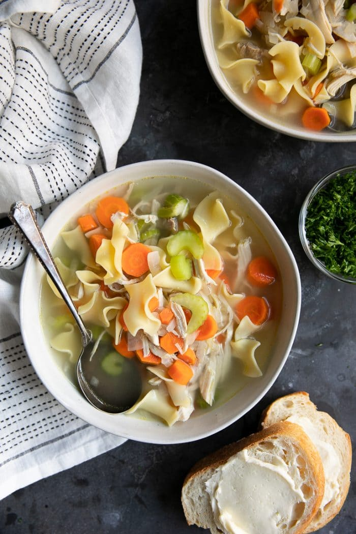 Bowl filled with chicken noodle soup with carrots, celery, and onions.