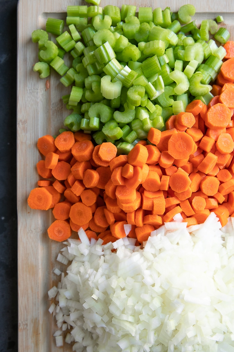 chopped celery carrots and onions on a wooden cutting board
