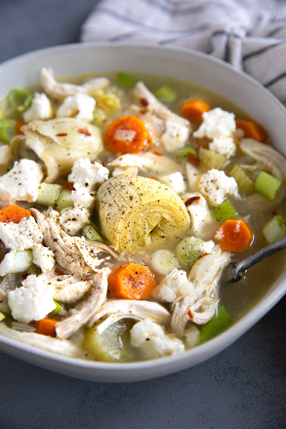 White bowl filled with lemon and artichoke chicken soup and garnished with crumbled feta cheese and red chili flakes.