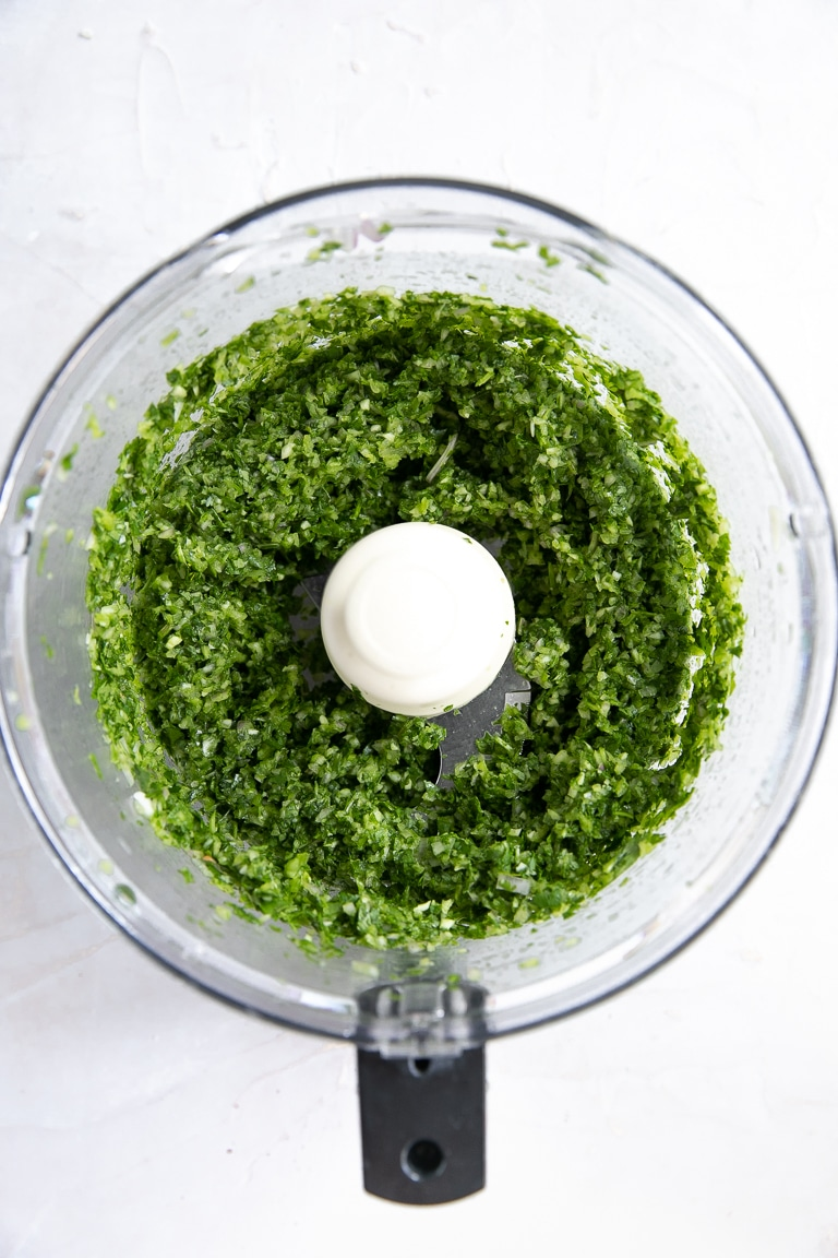 Food processor filled with finely processed coriander, garlic, and shallots.