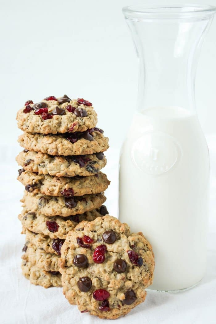 Large stack of cranberry chocolate chip cookies with a big jug of milk.
