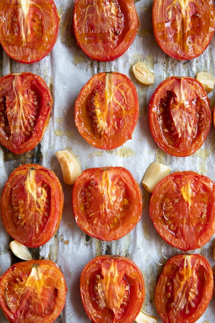 Halved roasted tomatoes with whole garlic cloves on a baking sheet.