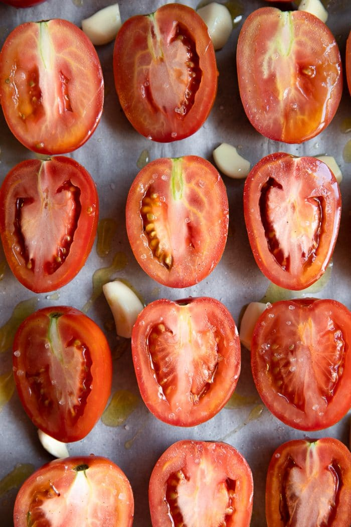 Halved Roma tomatoes with whole garlic cloves drizzled with olive oil and sprinkled with salt.