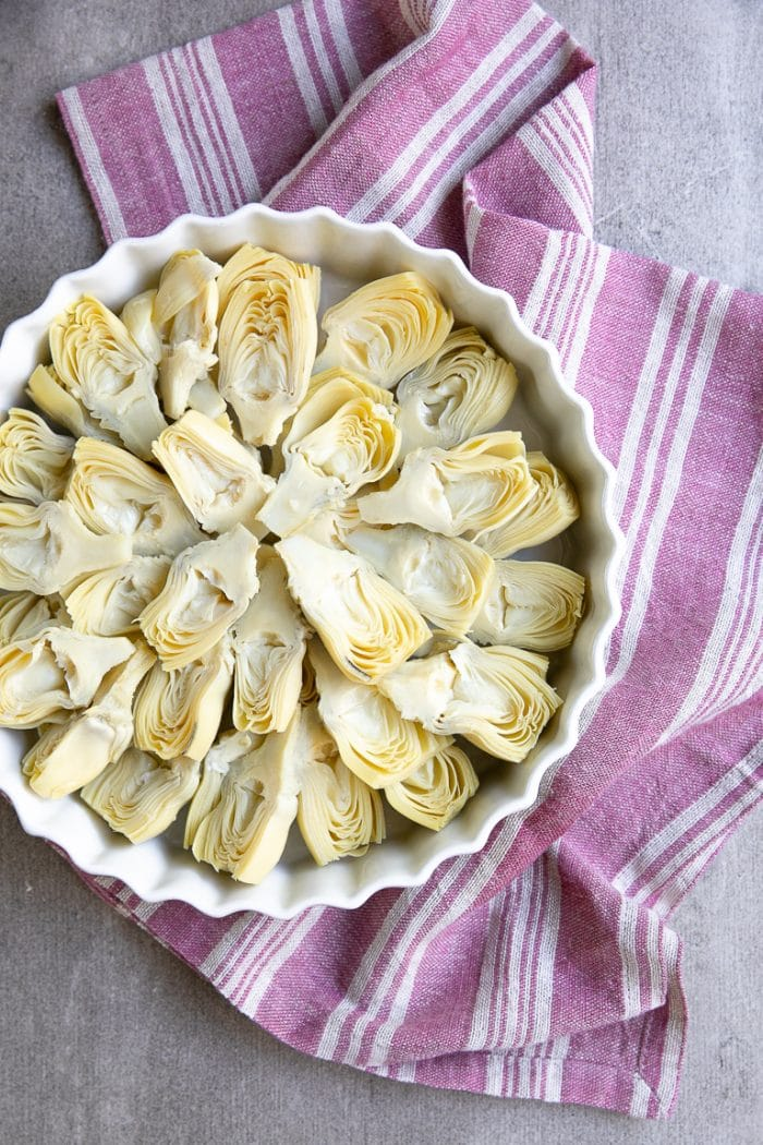 Tart pan filled with halved artichoke hearts