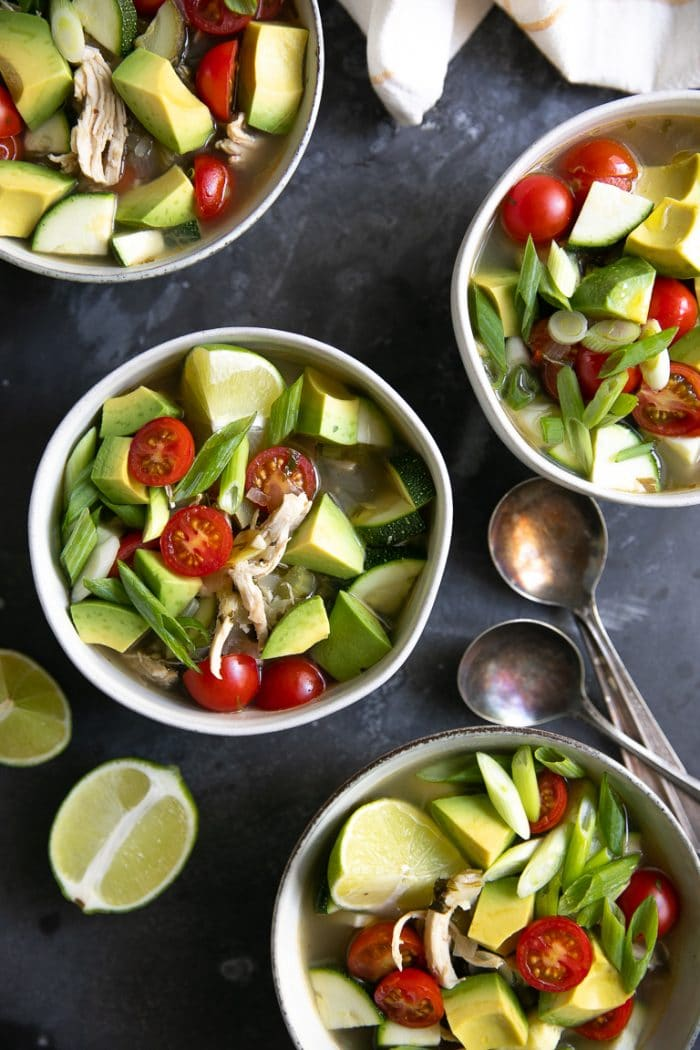Four white soup bowls filled with Easy Chicken Avocado Soup Recipe