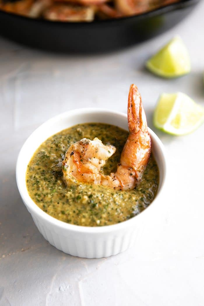 Large cooked shrimp resting in a small white serving bowl filled with Cilantro lime Sauce.