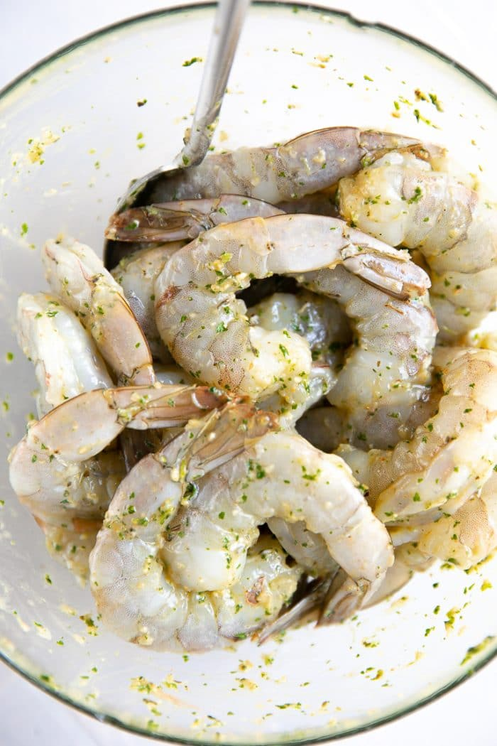 Prawns marinating in Cilantro Lime and Garlic in a clear glass dish.