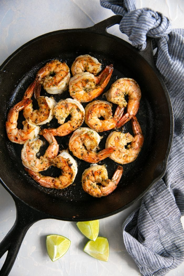 Overhead view of cilantro lime shrimp in a large cast iron skillet.