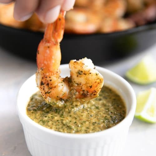 A close up of a Shrimp being dunked in sauce