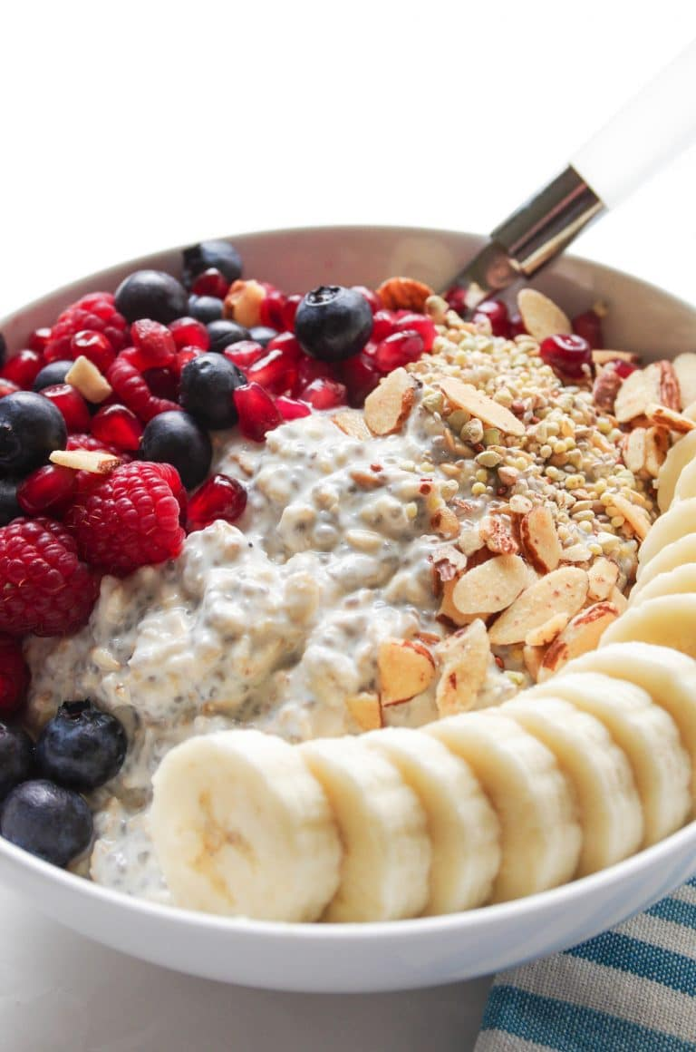 White bowl filled with simple Overnight Oats with and topped with Mixed Fruit including sliced bananas, berries, pomegranate arils, and nuts