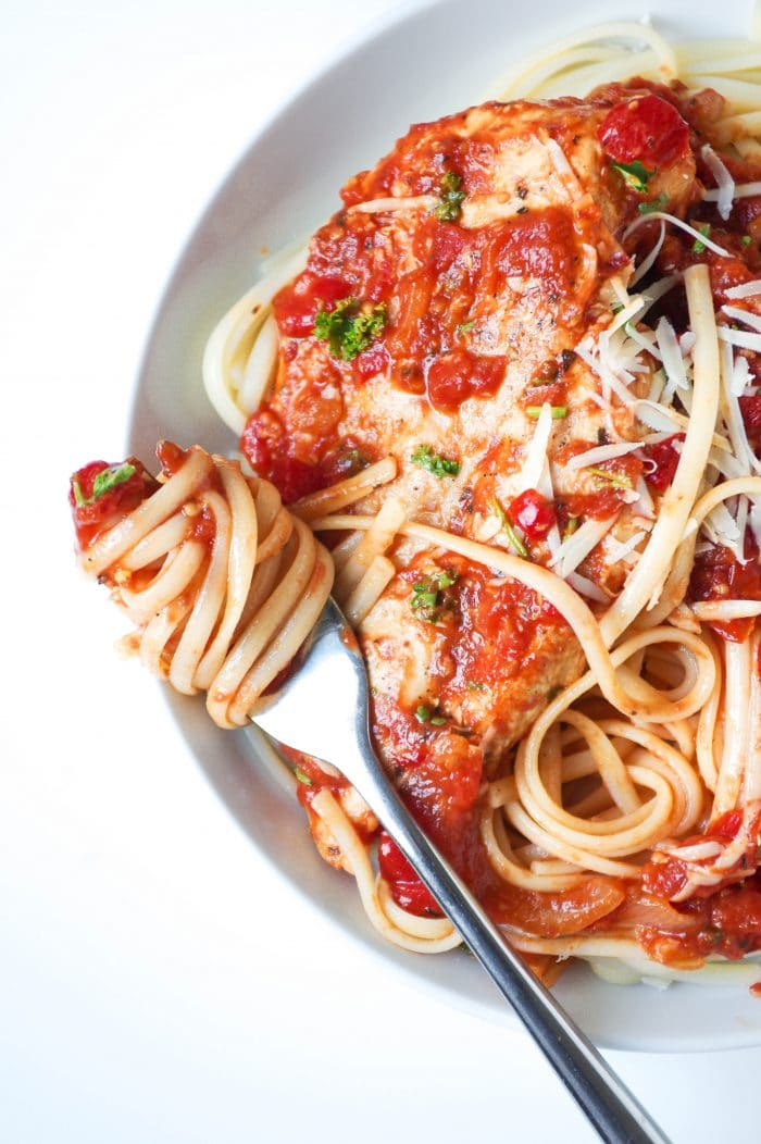Large white plate filled with linguine paste topped with roasted red pepper and tomato pasta sauce and whole chicken breast garnished with shredded parmesan cheese.