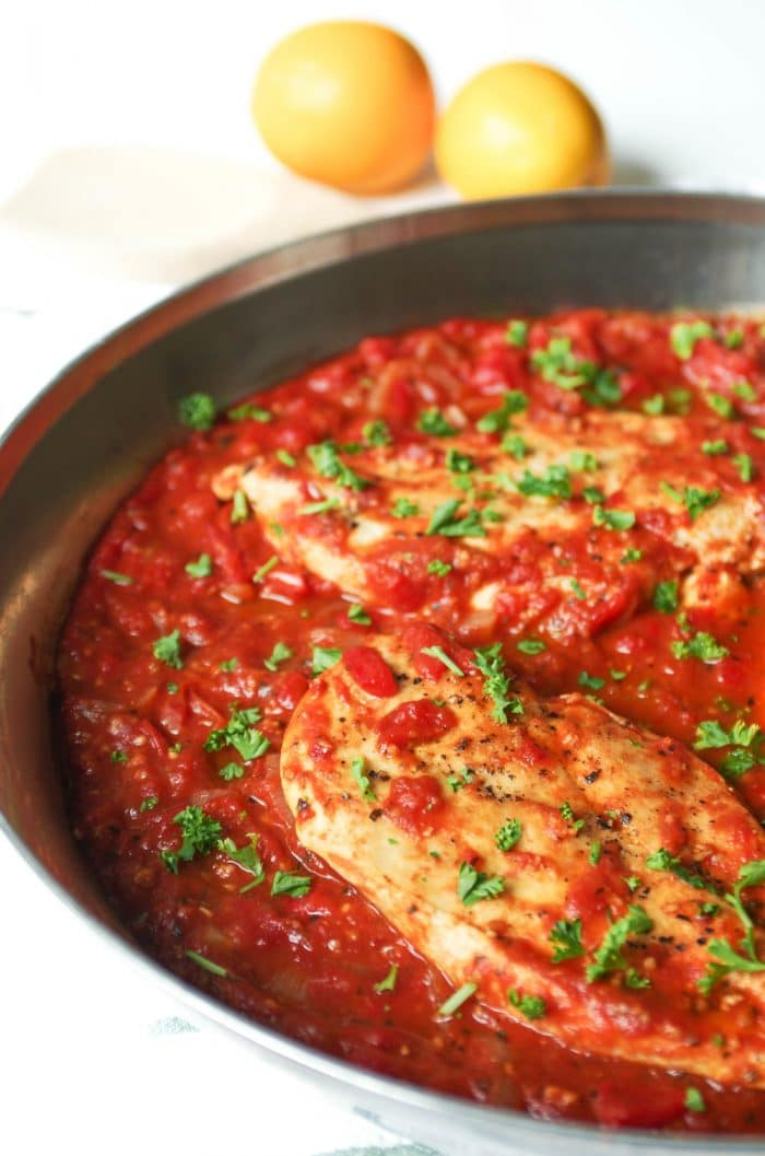 Large skillet filled with homemade roasted red pepper sauce and three whole chicken breasts garnished with chopped parsley.