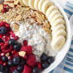 white bowl with sliced banana oats, over night yogurt, blueberries, raspberries, and blackberries