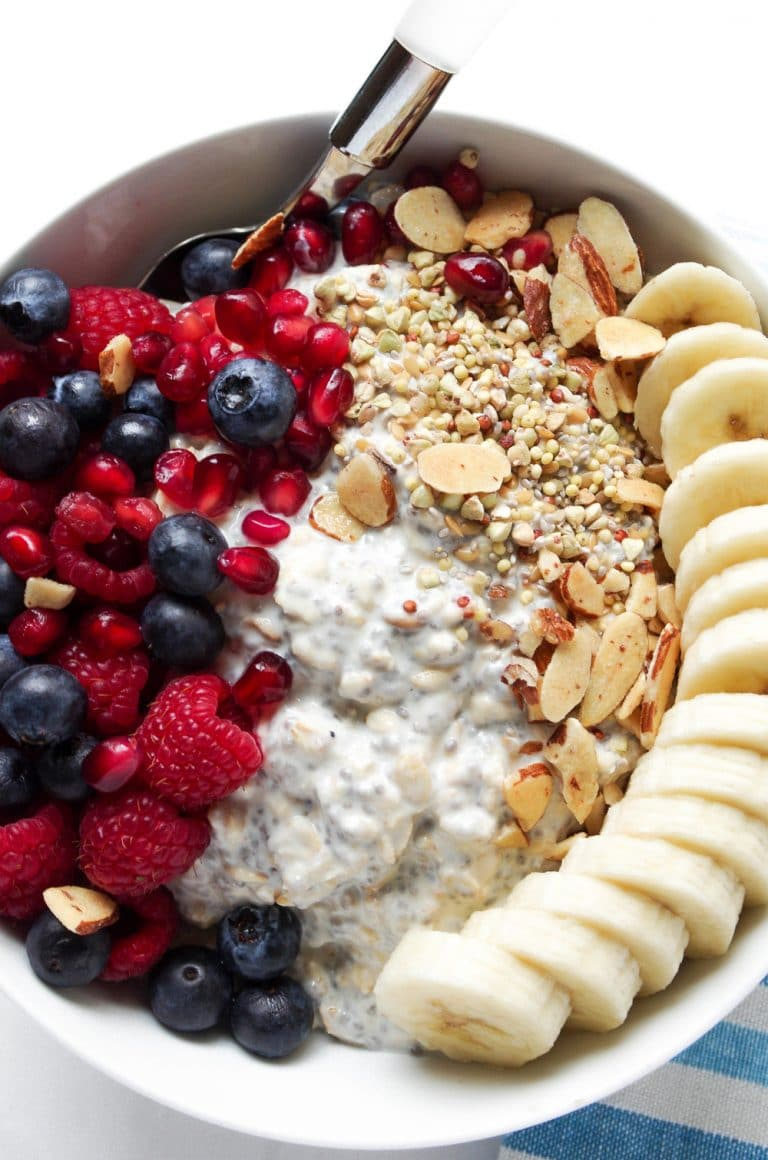 Overhead photo of white bowl with vanilla overnight oats loaded with berries, pomegranate arils, and sliced banana.