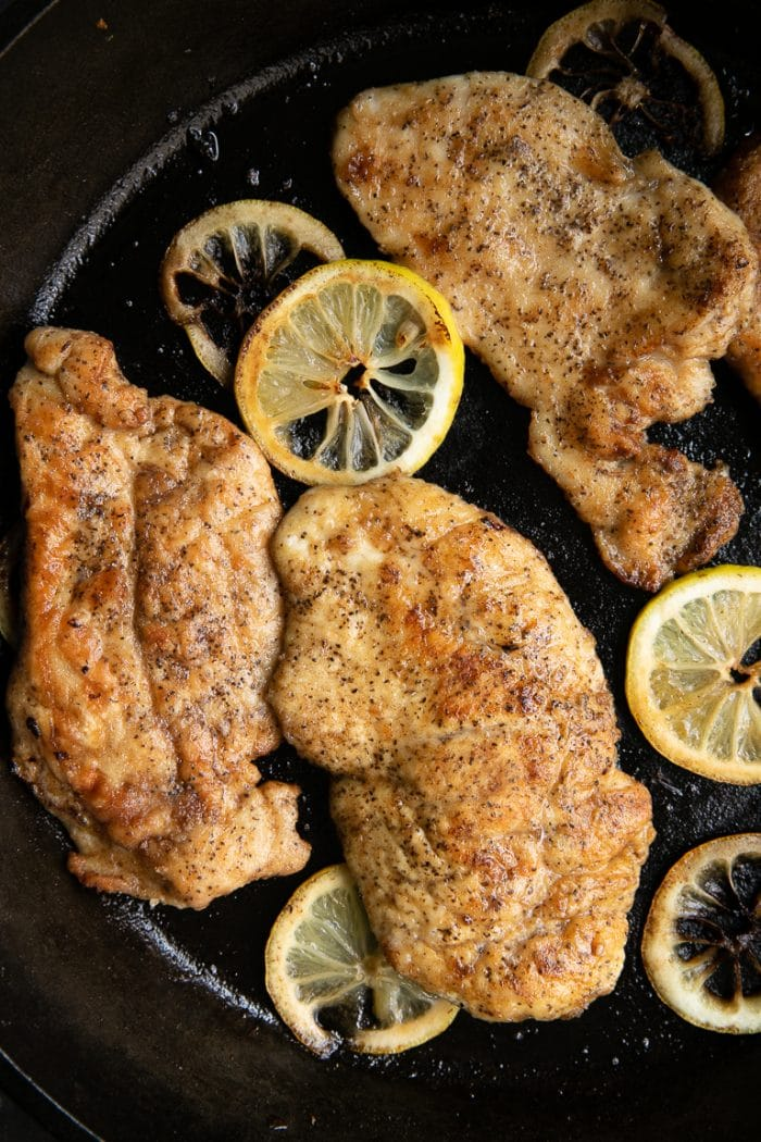 Cooked chicken cutlets in a large cast iron skillet with lemon slices.