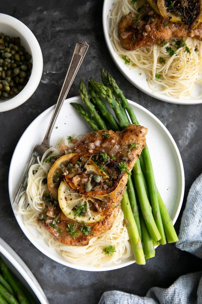 Overhead image of a white serving dish with angel hair pasta, chicken piccata and asparagus.