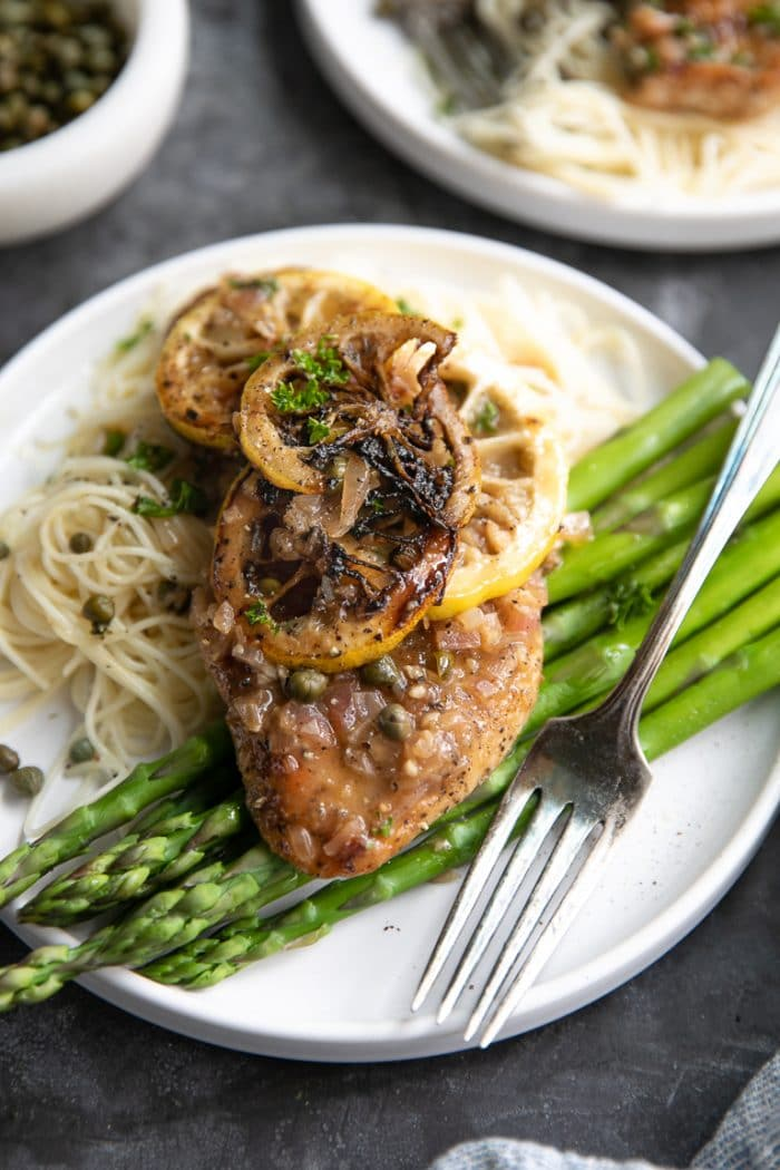 White plate with cooked noodles, asparagus, and one chicken piccata cutlet topped with lemon piccata sauce.