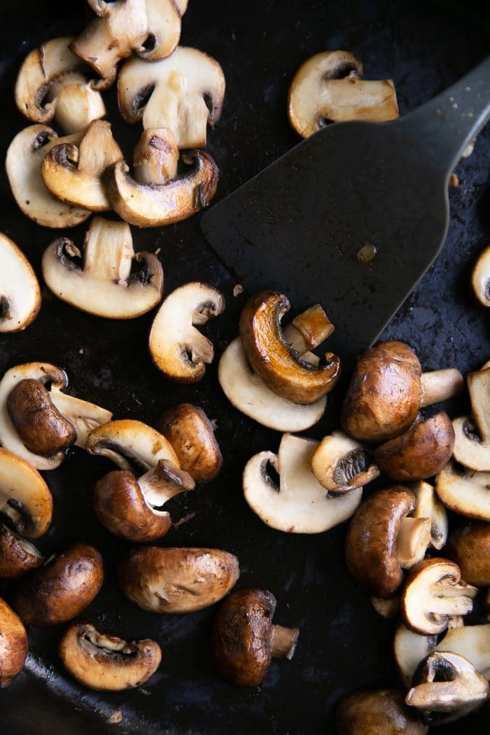 Cooking mushrooms in a large heavy-bottomed cast iron skillet.