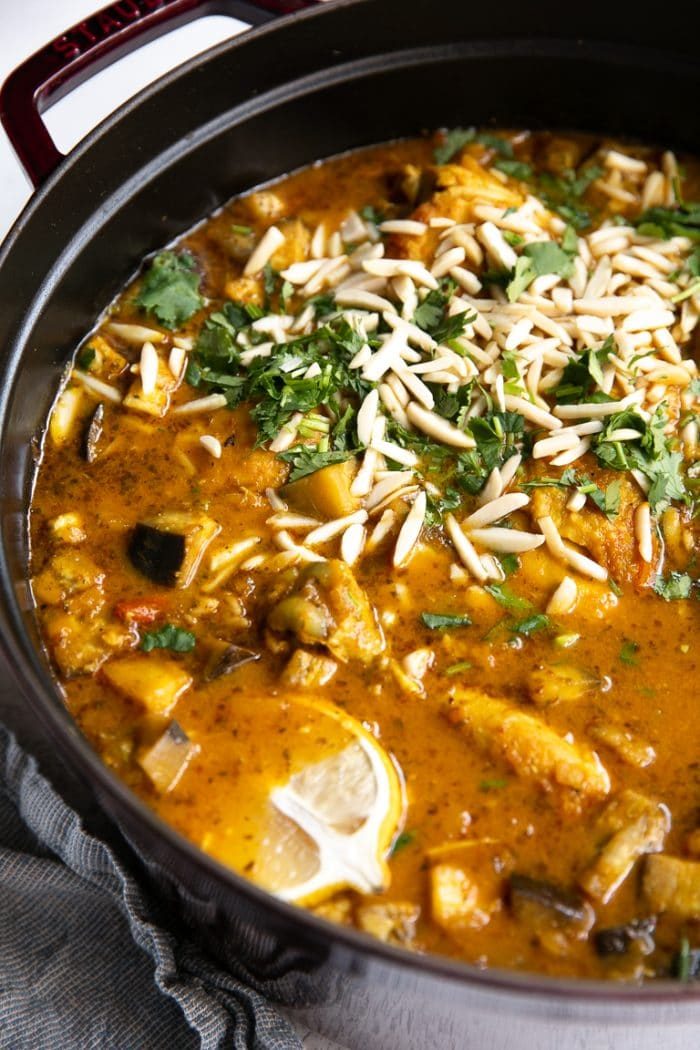 Large Dutch oven filled with Moroccan Chicken and garnished with fresh cilantro and slivered almonds.
