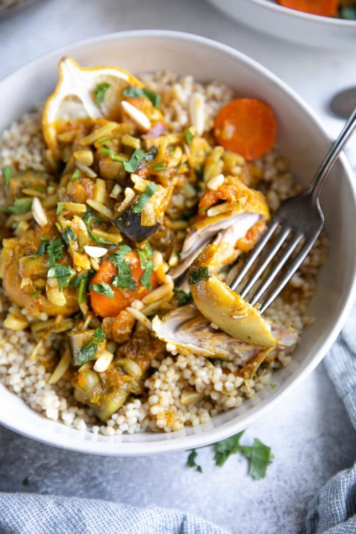 White bowl filled with couscous and topped with moroccan chicken with carrots, eggplant, and slivered almonds.