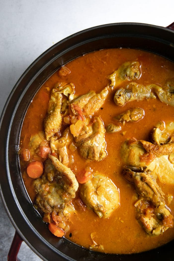 Large cast iron skillet filled with simmering Moroccan Chicken Stew.