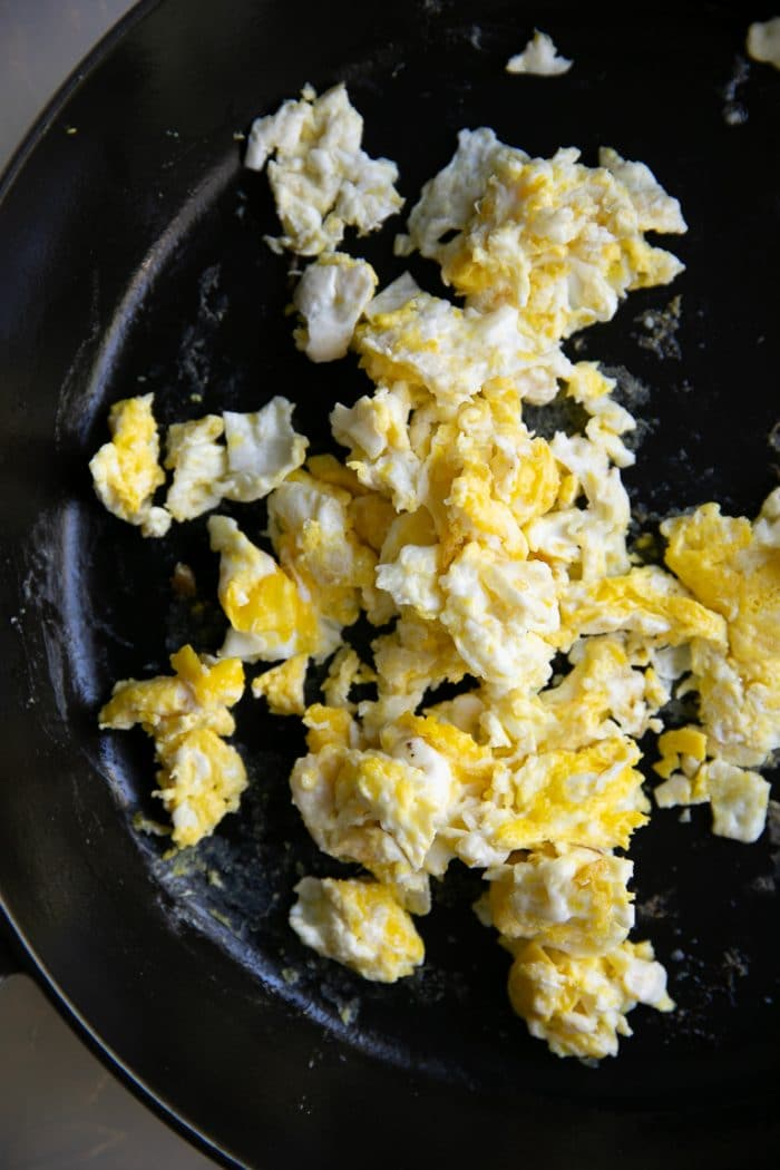 Scrambled eggs in a large heavy bottomed cast iron skillet.