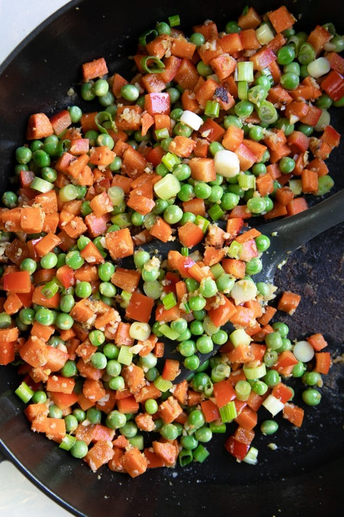Diced carrot and red bell pepper with peas cooking in a large heavy-bottomed skillet.