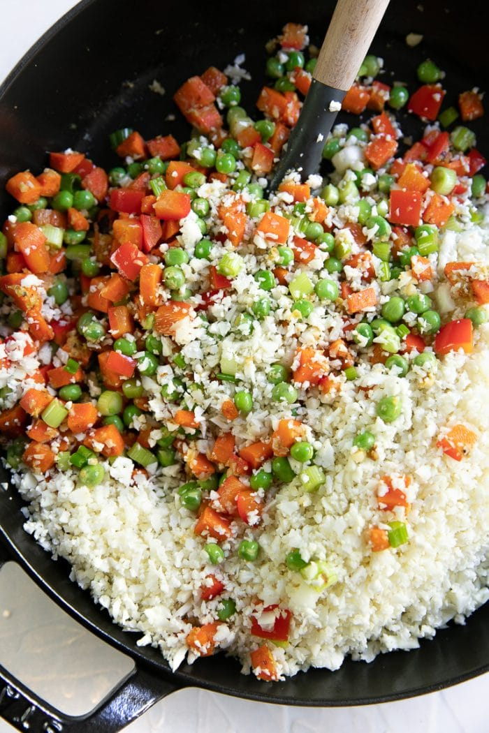 Sauteed diced carrots, bell pepper, and peas, mixed with raw cauliflower rice.